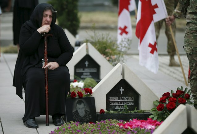 A woman mourns at the grave of a Georgian soldier killed during Georgia's conflict with Russia over the breakaway region of South Ossetia in 2008 during a ceremony at the memorial cemetery in Tbilisi, Georgia, August 8, 2015. (Photo by David Mdzinarishvili/Reuters)
