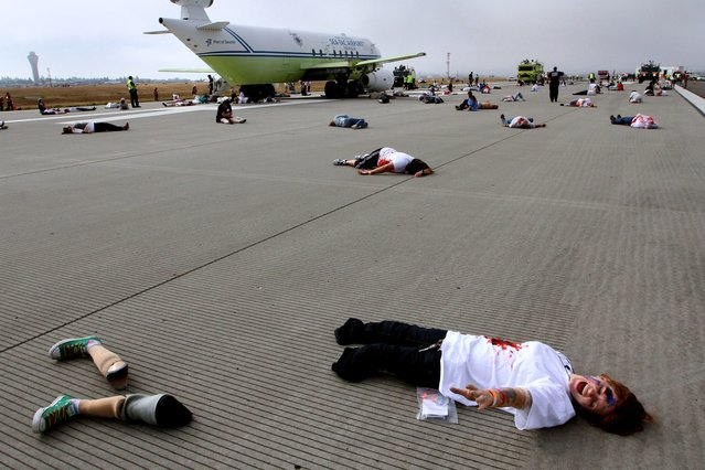 """Genessa Faye of Seattle yells out, """"Help me!"""" to responders to a mock airplane crash at SeaTac International Airport, Thursday, July 10, 2014. Approximately 300 volunteers took part in the mock crash site on the third runway at the airport. The volunteers were given clothes, makeup and a card which told him how badly they had been """"injured"""" and instructed them how to act. (Photo by Ellen M. Banner/AP Photo/The Seattle Times)"""