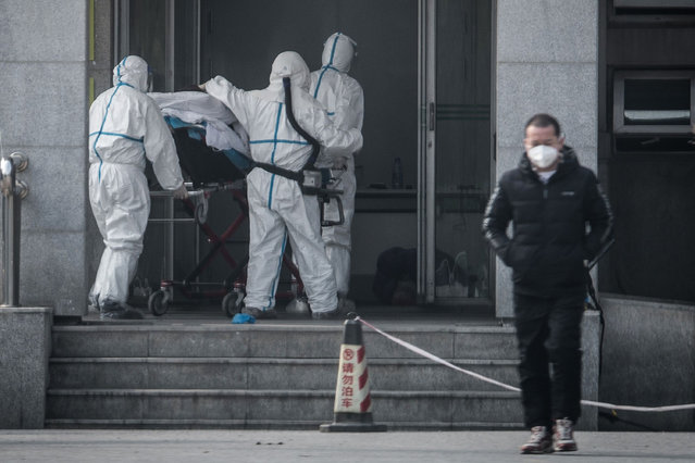 This file photo taken on January 18, 2020 shows medical staff members carrying a patient into the Jinyintan hospital, where patients infected by a mysterious SARS-like virus are being treated, in Wuhan in China's central Hubei province. A mysterious SARS-like virus has spread around China – including to Beijing – authorities said on January 20, 2020, fuelling fears of a major outbreak as millions begin travelling for the Lunar New Year in humanity's biggest migration. (Photo by AFP Photo/China Stringer Network)