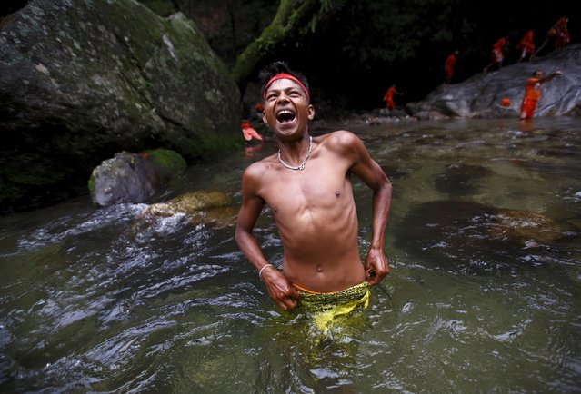 """A devotee reacts to cold water as he takes a dip while participating in the """"Bol Bom"""" pilgrimage in Kathmandu August 10, 2015. (Photo by Navesh Chitrakar/Reuters)"""