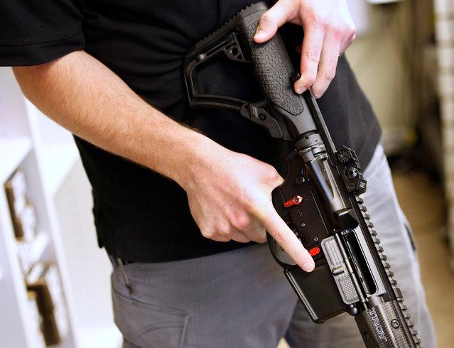 "Salesman, Ryan Martinez  holds an  AR-15 at the ""Ready Gunner"" gun store in Provo, Utah, U.S., June 21, 2016. (Photo by George Frey/Reuters)"