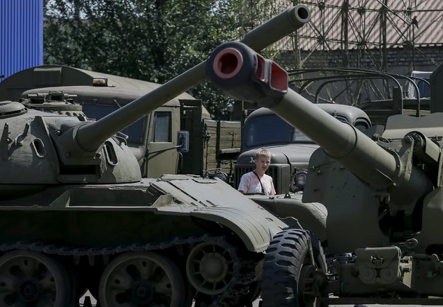A visitor looks at an old soviet tank and cannon at Phaeton museum in Zaporizhia, Ukraine, August 11, 2015. The museum stopped the restoration works of their collection of about 120 retro autos and motorcycles to help the Ukrainian army to restore military vehicles and equipment which will be used in the conflict in Ukraine eastern regions. (Photo by Gleb Garanich/Reuters)