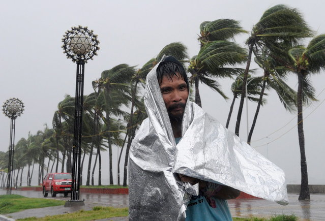 A man walks through heavy wind and rain as Typhoon Rammasun barrels across Manila on July 16, 2014. Typhoon Rammasun shut down the Philippine capital on July 16 as authorities said the first major storm of the country's brutal rainy season claimed at least one life and forced hundreds of thousands to evacuate. (Photo by Jay Directo/AFP Photo)