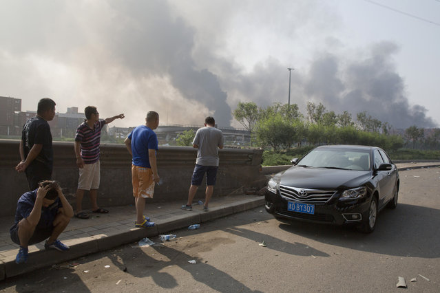 Residents gather near the site of an explosion at a port in northeastern China's Tianjin municipality, Thursday, August 13, 2015. Chinese state media reported huge explosions at the Tianjin port late Wednesday. (Photo by Ng Han Guan/AP Photo)