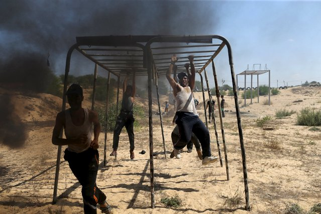 Young Palestinians swing across a monkey bar during a military-style exercise at a summer camp organized by Islamic Jihad movement, in Khan Younis in the southern Gaza Strip, August 13, 2015. (Photo by Ibraheem Abu Mustafa/Reuters)