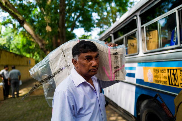 An electoral official carries ballot papers on his shoulder as he boards a bus to go to his respective polling station on the eve of the presidential election, in Colombo on November 15, 2019. (Photo by Jewel Samad/AFP Photo)