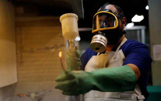 A worker from the Casa da Moeda do Brasil (Brazilian Mint) varnishes a Rio 2016 Olympic medal in Rio de Janeiro, Brazil, June 28, 2016. (Photo by Sergio Moraes/Reuters)