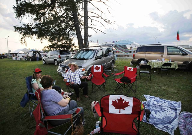 """A Portuguese-Canadian family enjoys a tailgate party during the intermission at an Azorean """"tourada a corda"""" (bullfight by rope) in Brampton, Ontario August 15, 2015. (Photo by Chris Helgren/Reuters)"""