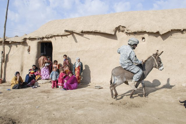 Van Agtmael was fascinated by the fighting when he first arrived, but he quickly became more interested in the quiet moments of war, like an American patrol that visited an isolated village outside of Mosul. The villagers were not even sure a war was going on. The soldiers took turns riding the donkeys. (Photo and caption by Van Agtmael/Harrison Jacobs/Magnum Photos)