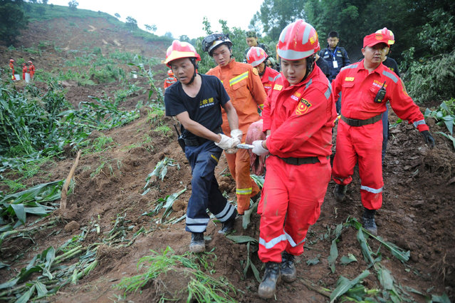 Rescue workers carry out a victim from the site of a landslide which killed at least 10 people in Bijie, Guizhou province, China, July 1, 2016. (Photo by Reuters/China Daily)