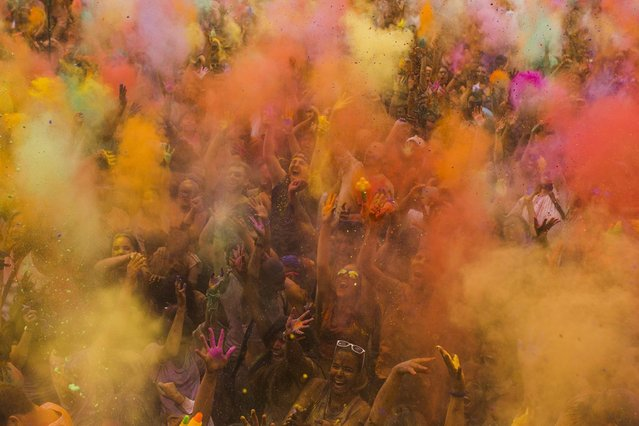 Revelers throw special coloured powders into the air during a Monsoon Holi Festival in Madrid, Spain, Saturday, August 9, 2014.The festival is based on the Hindu spring festival Holi, also known as the festival of colours where participants colour each other with dry powder and coloured water. (Photo by Andres Kudacki/AP Photo)