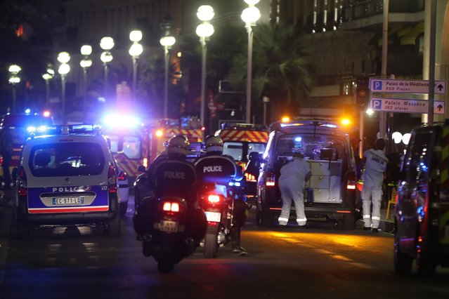 Police officers and rescue workers arrive at the scene of an attack on July 14, 2016, after a van ploughed into a crowd leaving a fireworks display in the French Riviera town of Nice. The mayor of the French city of Nice said dozens of people were likely killed after a van rammed into a crowd marking Bastille Day in the French Riviera resort today and urged residents to stay indoors. (Photo by Valery Hache/AFP Photo)