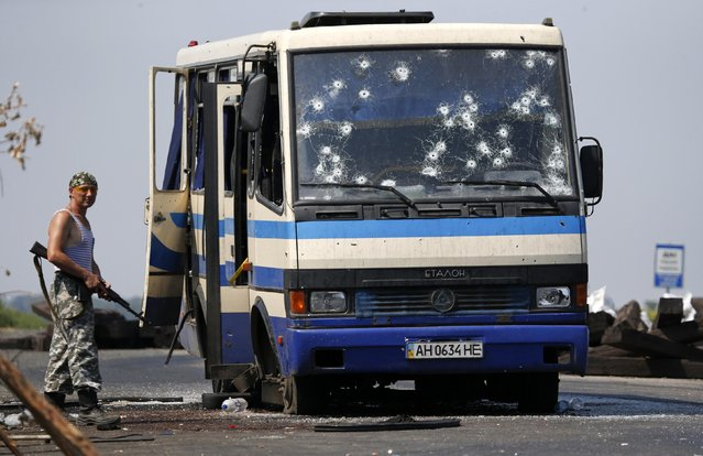 An armed pro-Russian separatist stands near a bus riddled with bullet holes at a checkpoint on the outskirts of Donetsk, August 13, 2014. Twelve Ukrainian nationalist fighters, battling a pro-Russian insurgency in eastern Ukraine, were killed early on Wednesday and an unknown number taken captive when rebels ambushed their bus, a spokesman for their group said. (Photo by Sergei Karpukhin/Reuters)