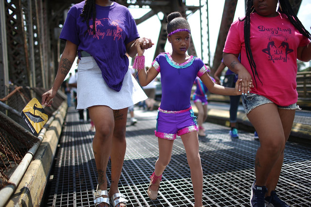 """A performer from """"Dazzling Lil Lady's"""" walks across a bridge crossing the Industrial Canal from the Lower Ninth Ward during a second line parade marking the 10th anniversary of Hurricane Katrina on August 29, 2015 in New Orleans, Louisiana. (Photo by Mario Tama/Getty Images)"""