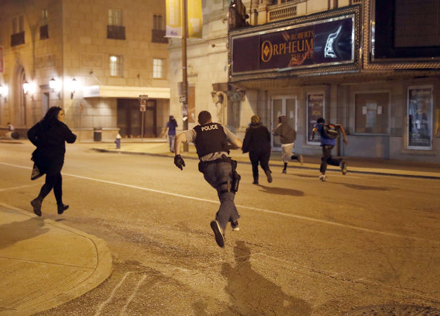 Police chase vandals as demonstrators march in response to a not guilty verdict in the trial of former St. Louis police officer Jason Stockley, Sunday, September 17, 2017, in St. Louis. Stockley was acquitted in the 2011 killing of a black man following a high-speed chase. (Photo by Jeff Roberson/AP Photo)
