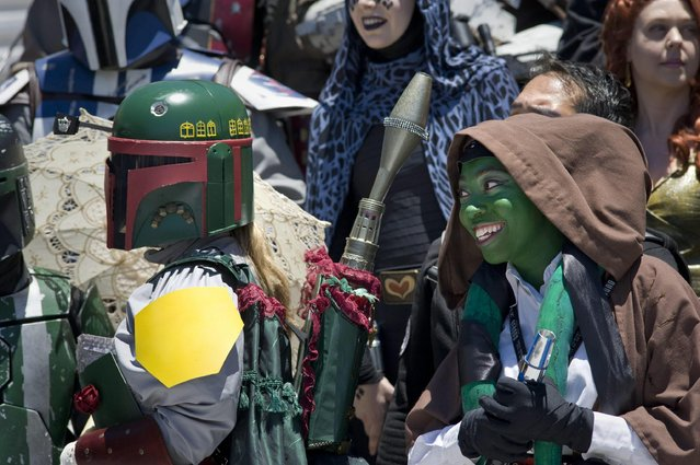 Bethany Jones (R), dressed as a green Twi'lek, a fictional species from the Star Wars universe, joins other cosplayers as they prepare for a group photo outside Comic Con 2016 in San Diego, California, USA, 22 July 2016. (Photo by David Maung/EPA)