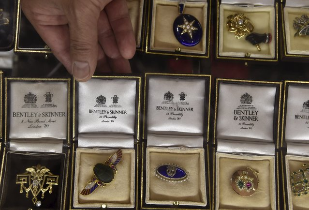 Jeweller Omar Vaja displays brooches with packaging covered in royal warrant insignia at Bentley and Skinner in central London, Britain, August 19, 2015. Bentley and Skinner, established in the 19th century, is a silversmith and jeweller to Queen Elizabeth. (Photo by Toby Melville/Reuters)