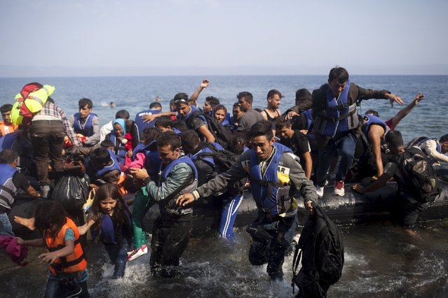 Syrian refugees jump off a dinghy as they arrive on the Greek island of Lesbos September 3, 2015. (Photo by Dimitris Michalakis/Reuters)