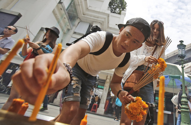 A visitor places a candle as an offering for Phra Phrom, the Thai interpretation of the Hindu god Brahma, at the Erawan Shrine in Bangkok, Thailand, Thursday, September 3, 2015. (Photo by Sakchai Lalit/AP Photo)