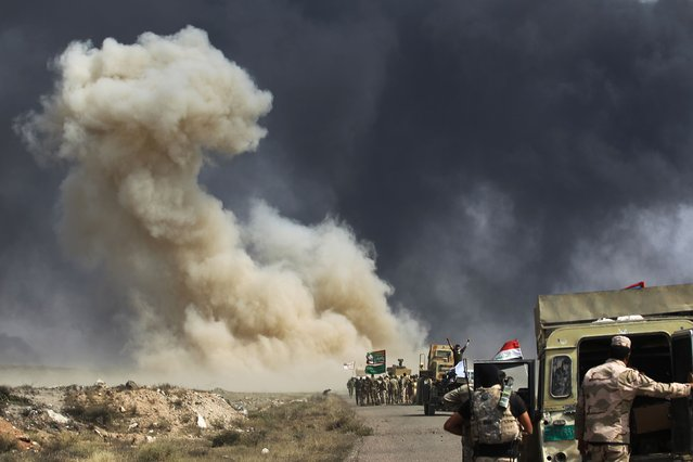 Smoke billow as Iraqi forces advance towards the Islamic State (IS) group's stronghold of Hawija on September 30, 2017 to recapture the town from the jihadists. Iraqi forces on September 29 launched an assault on the northern town of Hawija, one of the last bastions in the country still held by the Islamic State group, which is also under attack in neighbouring Syria. (Photo by Ahmad Al-Rubaye/AFP Photo)