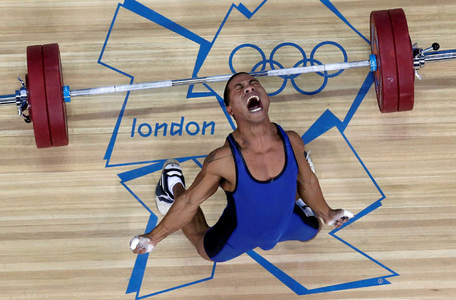 """Micronesia's Manuel Minginfel drops weights on the men's 62kg Group B weightlifting competition at the London 2012 Olympic Games in Britain July 30, 2012. Dominic Ebenbichler: """"I shot the picture with a robot remote camera which was fixed on the roof and that I triggered from the ground. The difficult part is to set it up prior to each weight lifting event. You have to preset the focus and shutter speed and as the athletes are not all the same size, a little bit of luck is involved as to whether the picture will be sharp. In this case everything came together perfectly: Minginfel dropped his weights and gestured upwards, we had set the focus on just the right position and what a result!. (Photo by Dominic Ebenbichler/Reuters)"""