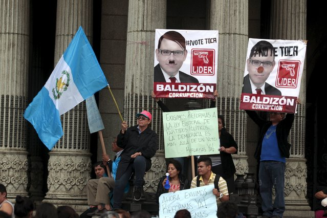 """Protesters hold Guatemalan flag and placards of Manuel Baldizon, presidential candidate of opposition Renewed Democratic Liberty Party (LIDER), as they take part in a protest against what they say is the death of Guatemalan democracy in Guatemala City, September 5, 2015. Guatemala on Sunday will hold a presidential election. The placard at the center reads, """"We demand reforms to the electoral law on political parties, democracy is more than a vote"""". (Photo by Jose Cabezas/Reuters)"""