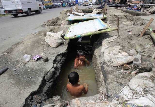 Children play in the murky waters of an open drainage being repaired by workers in Manila September 8, 2014. (Photo by Romeo Ranoco/Reuters)