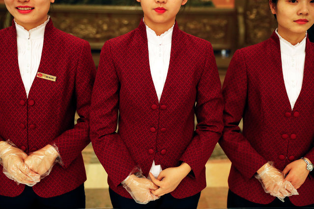 Hostesses stand behind the table with tea at the Great Hall of the People during the opening session of the 19th National Congress of the Communist Party of China in Beijing, China on October 18, 2017. (Photo by Damir Sagolj/Reuters)