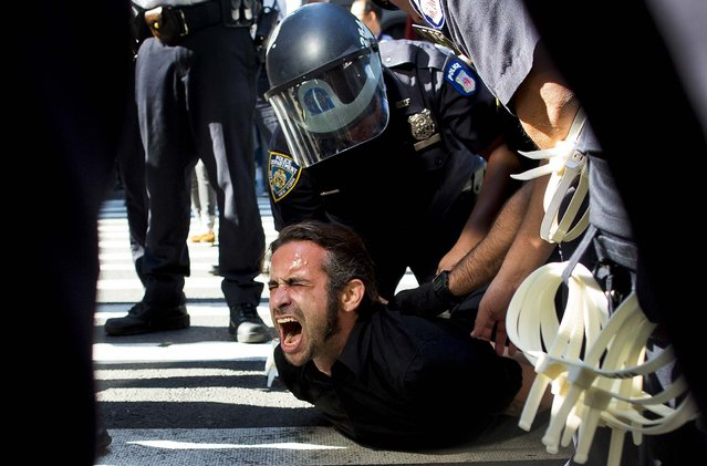 Occupy Wall Street protestor Chris Philips screams as he is arrested near Zuccotti Park in New York, on September 17, 2012. Multiple Occupy Wall Street protestors have been arrested during a march toward the New York Stock Exchange on the anniversary of the grass-roots movement. (Photo by John Minchillo/Associated Press)