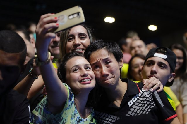 Jia Liu, center right, of Austria, sheds tears as she pauses for a selfie after her loss to Feng Tianwei, of Singapore, in a women's table tennis match at the 2016 Summer Olympics, Monday, August 8, 2016. (Photo by Jae C. Hong/AP Photo)