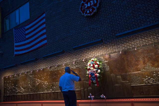 A member of the New York Fire Department salutes at the Wall of Remembrance, a memorial for fire fighters killed in the 9/11 attacks on the side of Engine 10, on the morning marking the 14th anniversary of the attacks, in New York September 11, 2015. Relatives of the nearly 3,000 people killed in the Sept. 11, 2001, attacks are due to gather in New York. (Photo by Andrew Kelly/Reuters)