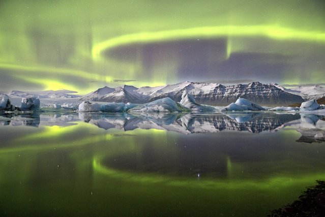 """Aurora over a glacier lagoon"". A vivid green overheaded aurrora pictured in Iceland's Vatnajokull National Park reflected almost symetrically in Jokulsrlon Glacier lagoon. A complete lack of wind and currrent combin in this sheltred lagoon scene to crete an arresting mirror effect giving the image a sensation of utter stillness. Despite theis there is motion on a suprising scale, as the loops and arcs of the aurora are shaped by the shifting forces of the Earth's magnetic field. (Photo by  James Woodend/The Astronomy Photographer of the Year 2014 Contest)"