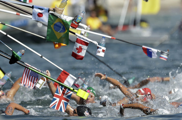 Swimmers make their way through a feeding station during the women's marathon swimming competition of the 2016 Summer Olympics in Rio de Janeiro, Brazil, Monday, August 15, 2016. (Photo by Gregory Bull/AP Photo)
