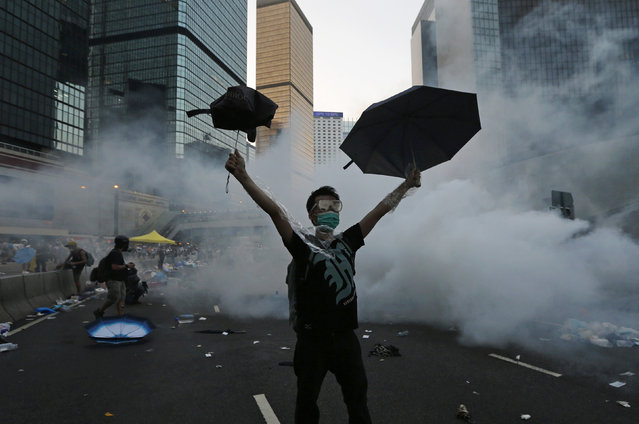 A protester raises his umbrellas in front of tear gas which was fired by riot police to disperse protesters blocking the main street to the financial Central district outside the government headquarters in Hong Kong, September 28, 2014. (Photo by Tyrone Siu/Reuters)