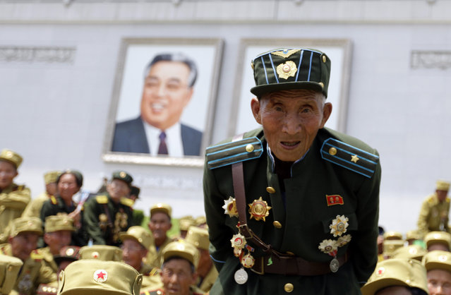 A Korean War veteran stands in front of a giant portrait of late North Korean leader Kim Il-sung after a parade to mark the 60th anniversary of the signing of a truce in the 1950-1953 Korean War at Kim Il-sung Square, in Pyongyang, July 27, 2013. (Photo by Jason Lee/Reuters)