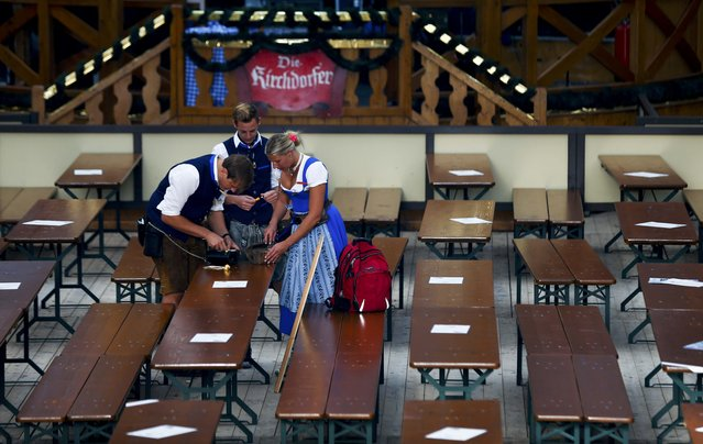 Waiters and waitresses chat inside a tent before the opening of the 182nd Oktoberfest in Munich, Germany, September 19, 2015. Millions of beer drinkers from around the world will come to the Bavarian capital over the next two weeks for Oktoberfest, which starts today and runs until October 4, 2015. (Photo by Michael Dalder/Reuters)
