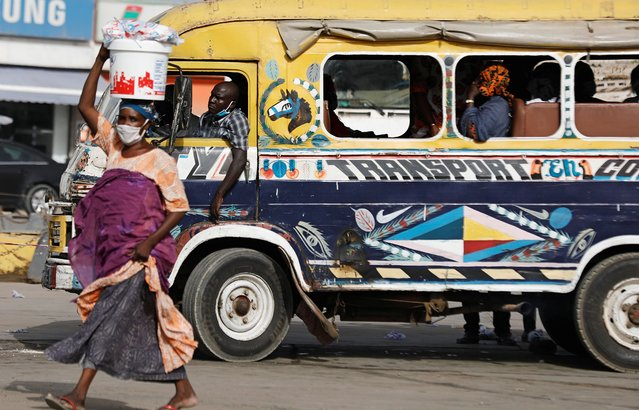"""A street vendor walks past a driver waiting for passengers to occupy his bus called """"Car Rapide"""", amid the outbreak of the coronavirus disease (COVID-19), at a bus station in Dakar, Senegal, June 24, 2020. (Photo by Zohra Bensemra/Reuters)"""