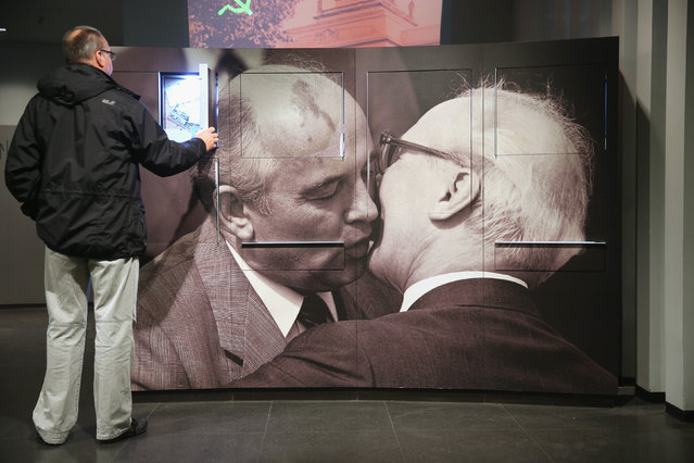 A visitor looks at an exhibit next to a photograph of former Soviet leader Mikhail Gorbachev (L) embracing former East German communist leader Erich Honecker at the DDR Museum on October 8, 2014 in Berlin, Germany. (Photo by Sean Gallup/Getty Images)