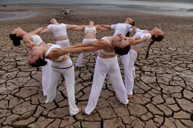 Women perform yoga on a dried river bank in Yunyang county, Chongqing Municipality, August 21, 2016. (Photo by Reuters/China Daily)