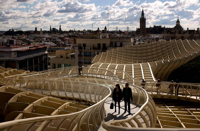 A couple walk along of one the corridors of the Metropol Parasol, overseeing the old city and the Giralda Cathedral of Seville, November 18, 2012. The Metropol Parasol by Jurgen Mayer H. Architects claims to be the world's largest wooden structure. (Photo by Emilio Morenatti/Associated Press)