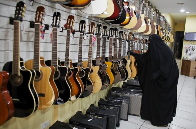 Gisele Marie, a Muslim woman and professional heavy metal musician, looks at guitars at a shop selling musical instruments in Sao Paulo August 13, 2015. (Photo by Nacho Doce/Reuters)