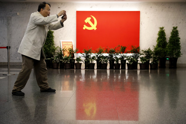 A man takes a smartphone photo near a Communist flag on display at the museum of the first National Congress of the Communist Party of China in Shanghai, China, Sunday, November 19, 2017. Chinese tourists and visitors have flocked to the museum in Shanghai since President Xi Jinping made a visit with the newly-installed line-up of top party leaders late last month. During the leaders' visit, they were depicted on state television reaffirming their party oaths with their fists raised. (Photo by Andy Wong/AP Photo)