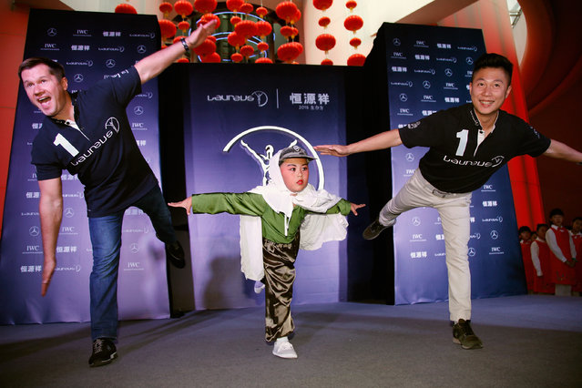 Laureus Academy Member Alexey Nemov and Laureus Ambassador Li XiaoPeng perform with a child at Oriental Pearl Tower on October 17, 2014 in Shanghai, China. (Photo by Kevin Lee/Getty Images for Laureus)