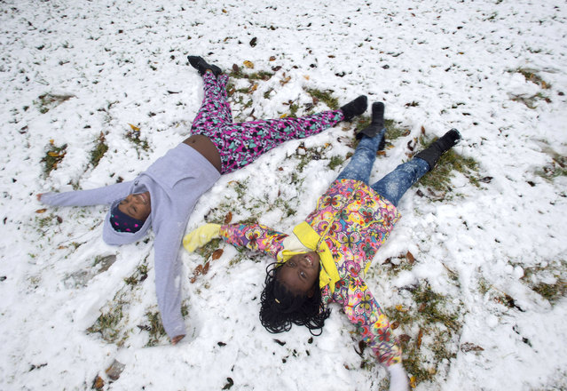 Kasey Brown, 11, left, and her friend Destiny Minor, 7, make snow angels on a lawn on their street, West Grant, Friday, December 8, 2017, after an unusual snowfall in Baton Rouge, La. Kasey's father Dlaniger Brown said the girls were enjoying the snow, and had been outside several times already, but were especially happy just to be home from school for the day. (Photo by Travis Spradling/The Advocate via AP Photo)