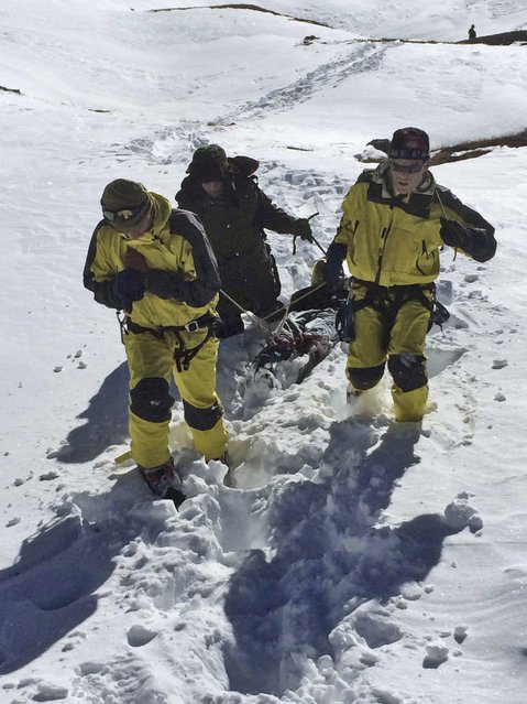 In this photo released by the Nepalese Army, rescue team members carry a victim of an avalanche before they airlift the body from Thorong La pass area, in Nepal, Thursday, October 16, 2014. Search teams in army helicopters rescued dozens of stranded foreign trekkers and recovered more bodies of victims of a blizzard and avalanches in the mountains of northern Nepal on Thursday. (Photo by AP Photo/The Nepalese Army)