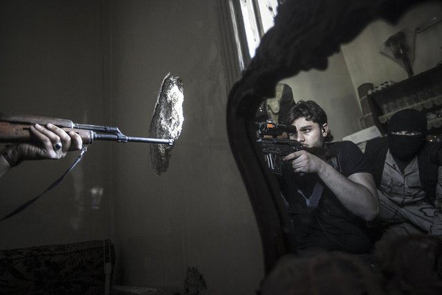 In this October 29, 2012 file photo, a rebel sniper aims at a Syrian army position, seen with another rebel fighter reflected in a mirror, in a residential building in the Jedida district of Aleppo, Syria. (Photo by Narciso Contreras/AP Photo)