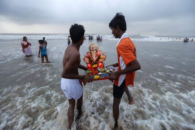 Young Indian devotees carry a representation of the elephant-headed Hindu god Lord Ganesha into the Arabian Sea during celebrations of the god's birth in Mumbai, India, 21 September 2015. During the Ganpati festival, celebrated as the birthday of Lord Ganesha, devotees worhsip representations of the Hindu deity at hundreds of pandals, makeshift tents, before they are taken into the waters. (Photo by Divyakant Solanki/EPA)