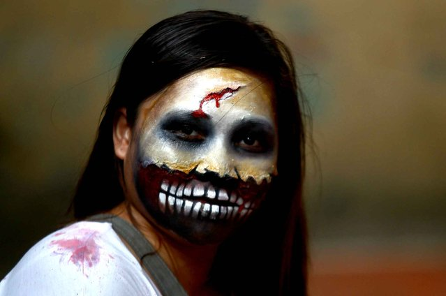 A woman wears zombie make-up during a Zombie Zumba Party in Mandaluyong City, the Philippines, October 26, 2014. (Photo by Rouelle Umali/Xinhua)
