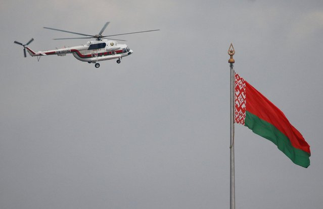A helicopter believed to be carrying Belarusian President Alexander Lukashenko flies over the Independence Palace during an opposition demonstration to protest against presidential election results, in Minsk, Belarus on August 23, 2020. (Photo by Vasily Fedosenko/Reuters)