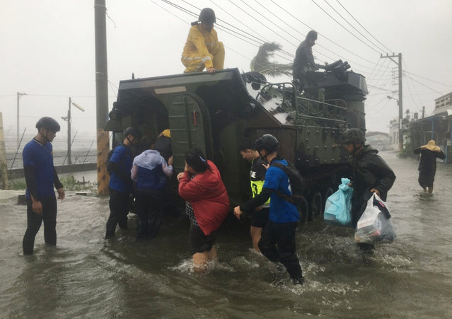This photo by Taiwan agency CNA Photo shows residents affected by super typhoon Meranti being evacuated on a military armoured vehicle in southern Pingtung county on September 14, 2016. Parts of Taiwan were brought to a standstill September 14 as super typhoon Meranti skirted past the island's southern tip, bringing the strongest winds in 21 years and disrupting traffic ahead of a major holiday. (Photo by AFP Photo/Stringer)